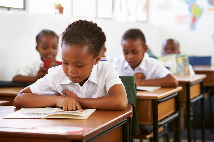 Schoolgirl reading at her desk in elementary school lesson